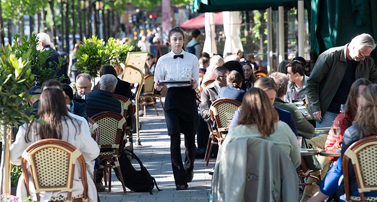 En servitris går med en bricka på en uteservering.