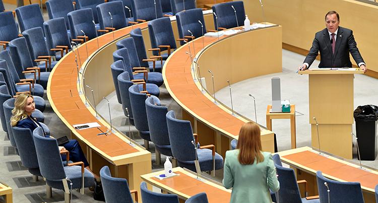 Stefan Löfven står i talarstolen i riksdagen. Det är många tomma stolar framför honom. Två kvinnor lyssnar.