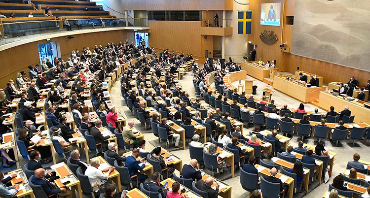 En bild över hela riksdagen sal. Politikerna sitter två och två i sina bänkar.