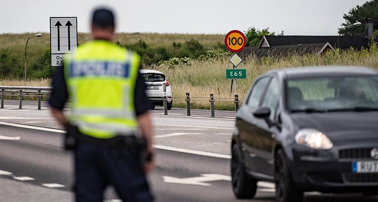 En rygg på en polis. Polisen står vid en väg. Två bilar syns i bakgrunden.