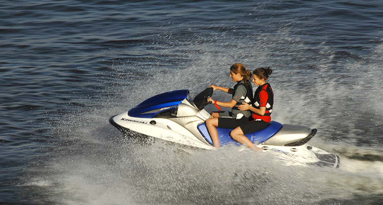 En vattenskoter kör i ful fart. Vattner stänker åt sidorna. Två flickor sitter på den.