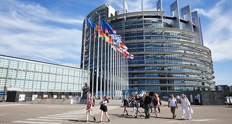 Människor går framför en stor rund byggnad. Framför finns flera flaggstänger med olika flaggor.