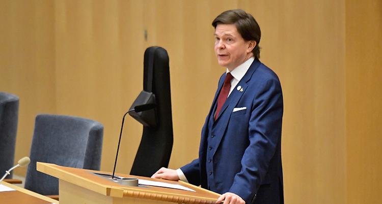 Han står framför en mikrofon i riksdagen.