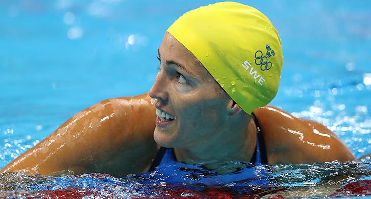 Therese Alshammar i bassängen. Hon har sommar färdigt och tittar åt sidan och ser glad ut. Hon har en gul badmössa.