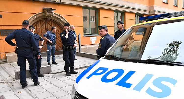 Poliser och en polisbuss märkt med polis står på plattläggningen utanför ett orangefärgat stenhus
