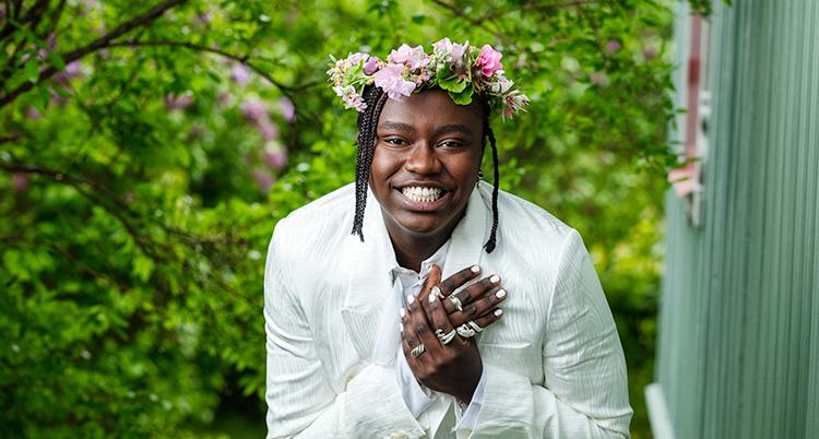 Han har en krans med blommor i håret. Han ler.