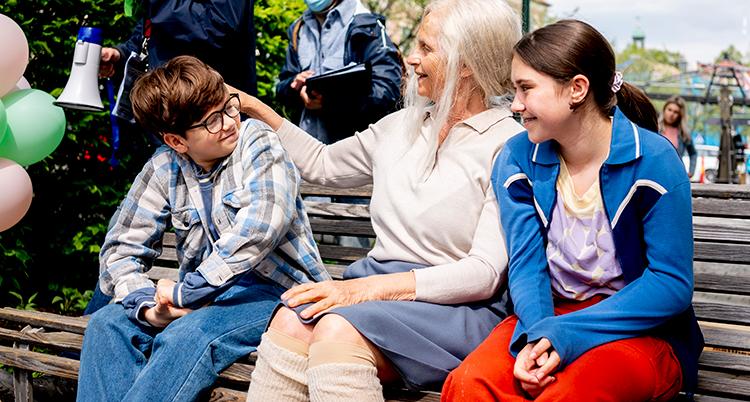 Skådespelarna i den nya filmen om Lasse och Maja sitter tillsammans en bänk.
