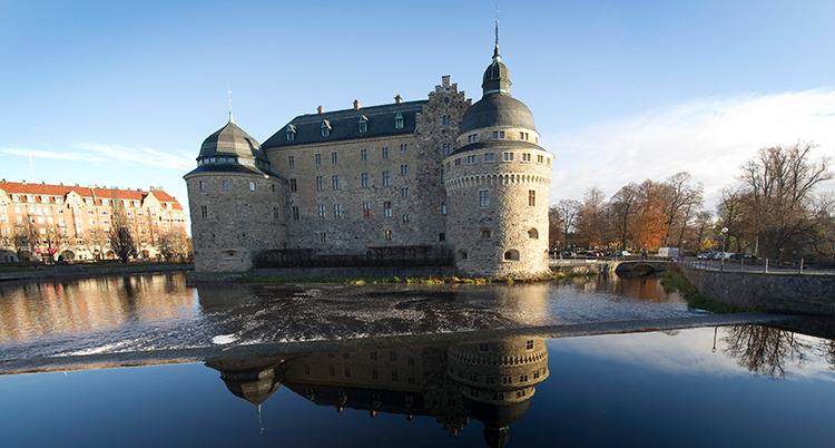 Ett slott omgivet av vatten och andra hus. Himlen är blå.
