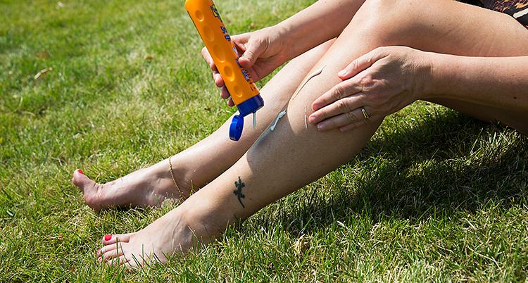 Bild på personer som smörjer sitt ben med solkräm.