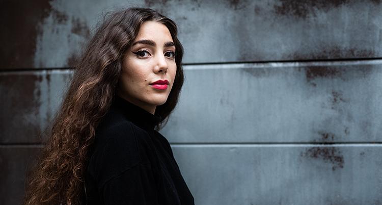 Giną Dirawi tittar in i kameran. Hon har långt mörkt hår och rött läppstift. Hon står framför en grå vägg.