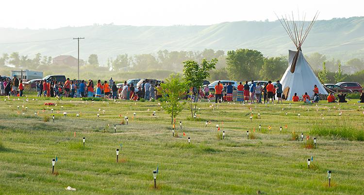 På ett fält med gräs finns flaggor och ljus. Längre bort står en grupp med människor.