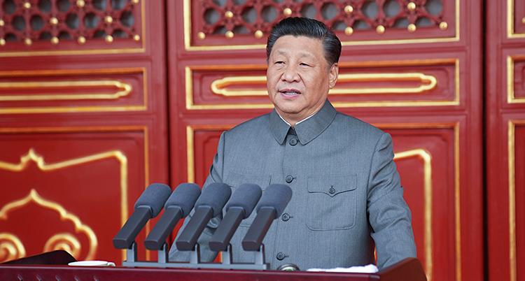 Han står och pratar i en talarstol. Det finns flera mikrofoner.