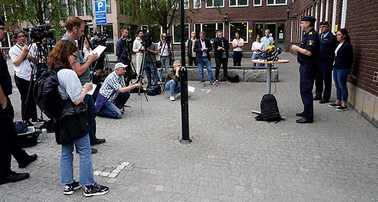 Tre poliser står utanför ett hus. De har ett litet bord där det står mikrofoner. Framför dem finns en massa journalister med anteckningsblock och kameror.