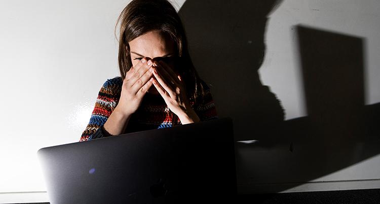 en kvinna sitter framför en dator och ser rädd ut. Hon har händerna i ansiktet.