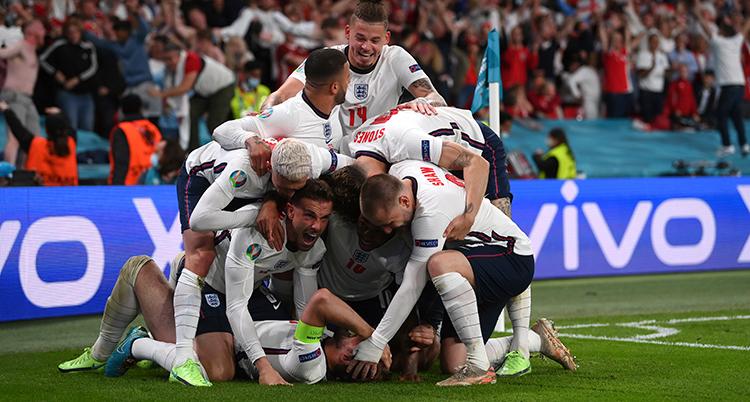 Englands spelare i vitt kramas på planen.