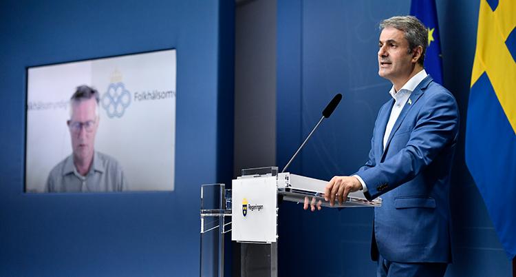 Ibrahim Baylan från regeringen pratar på presskonferens. Bredvid honom en tv-skärm där Anders Tegnell syns.