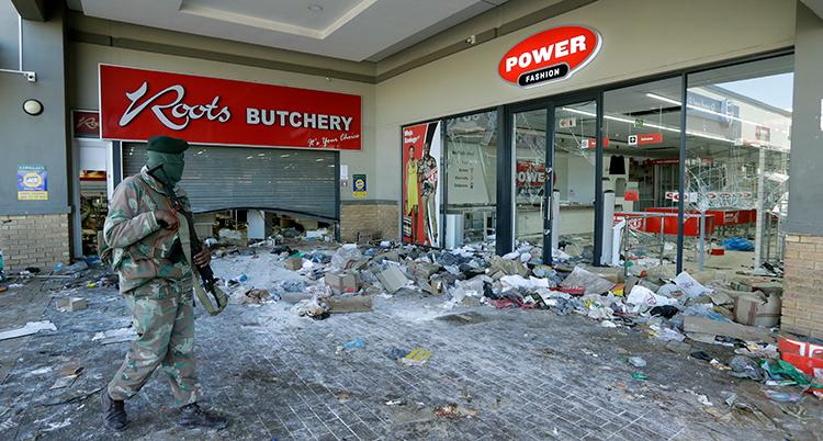 En sydafrikansk soldat kollar på en förstörd affär.