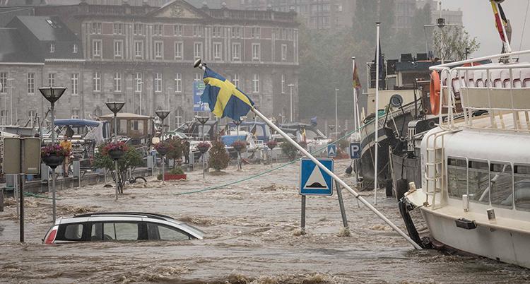 En bild från en stad som blivit översvämmad. Vatten står upp till rutorna på en bil.