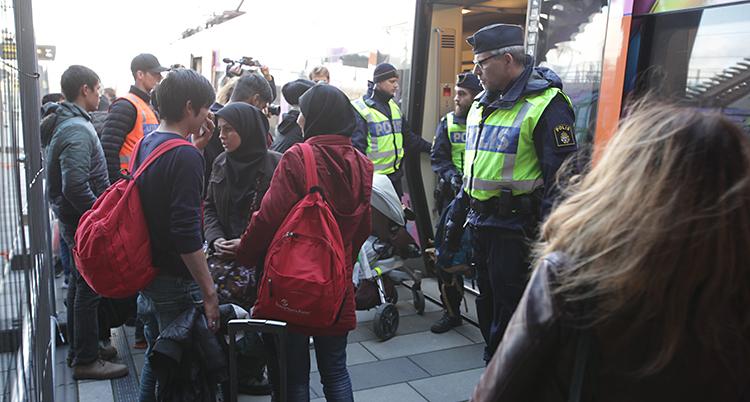 Utanför en tågstation. Där står flera människor och några poliser.