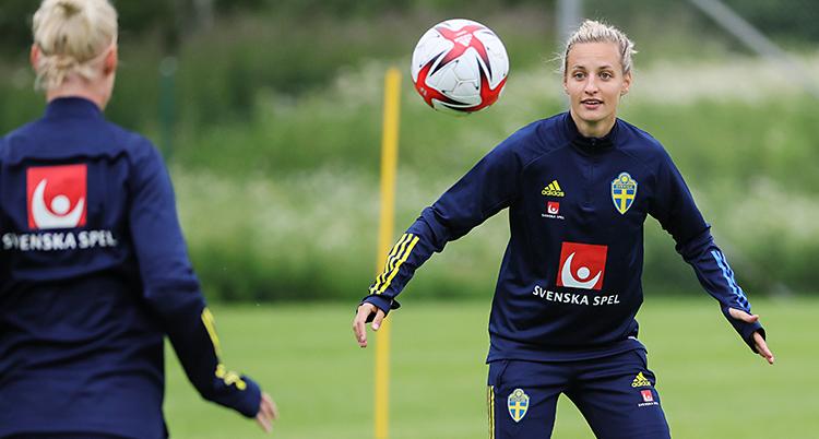 En träning för fotboll. Bollen är i luften. Nathalie Björn tittar på bollen och gör sig redo. Hon har blå kläder med den svenska flaggan på.
