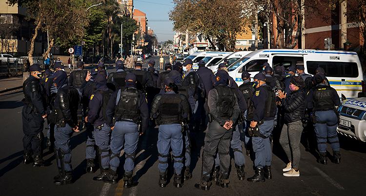 En grupp med ungefär 20 poliser står på en gata.