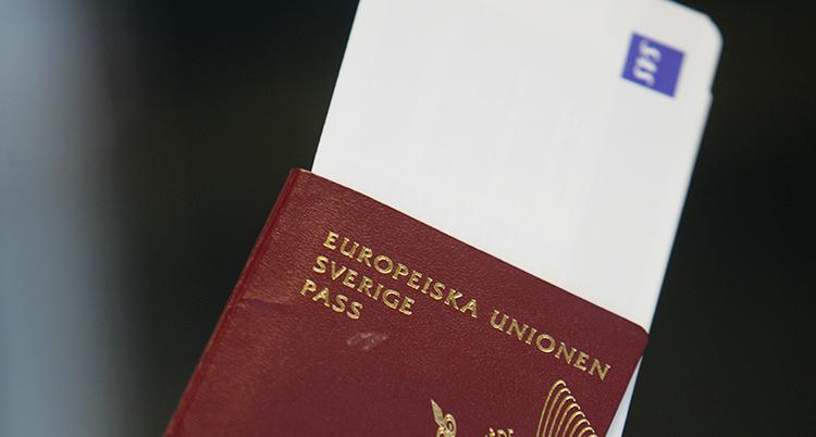Bilden visar ett rött pass. Det är ett svenskt pass.