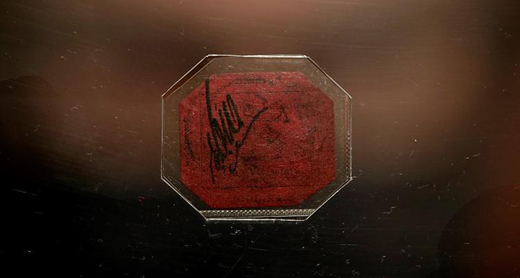 Vi ser ett rött frimärke med åtta kanter. Frimärket är inplastat.