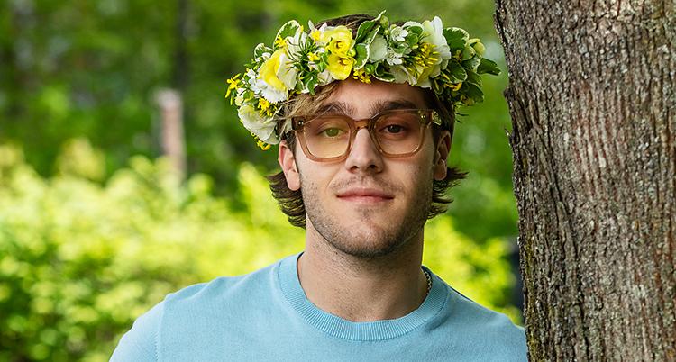 Han står vid ett träd. Han tittar in i kameran. Han har glasögon och en krans med blommor på huvudet.