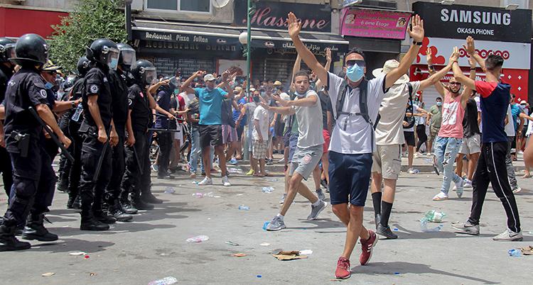 Några unga män är ute på gatan och protesterar. Några poliser står bredvid och vaktar.