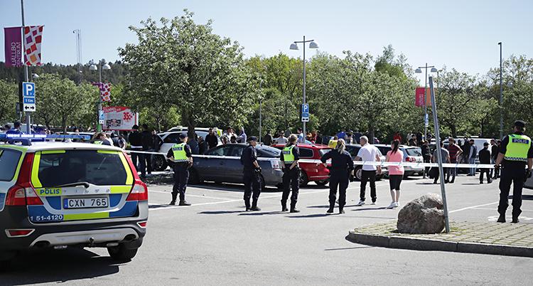 En parkeringsplats i Hjällbo. Poliser är ute och jobbar. De har spärrat av platsen med ett band.