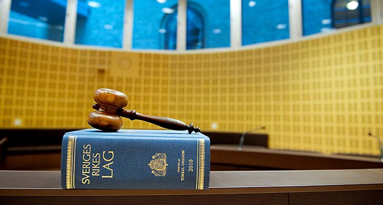 Från en sal i en domstol. En bok med lagar ligger på ett bord. Ovanpå boken finns en klubba av trä.