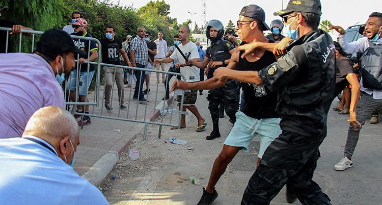 Flera personer har samlats på gatan utanför riksdagens hus. Flera poliser är också där.