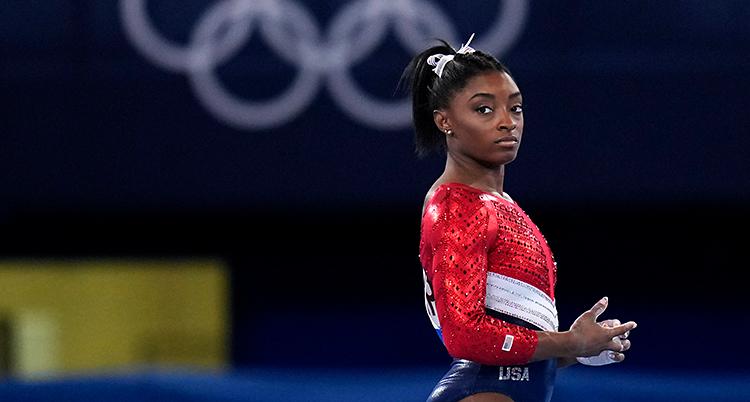 Simone Biles från en tävling i OS. Hon ser allvarlig ut. Hon har en dräkt som är röd, vit och blå.
