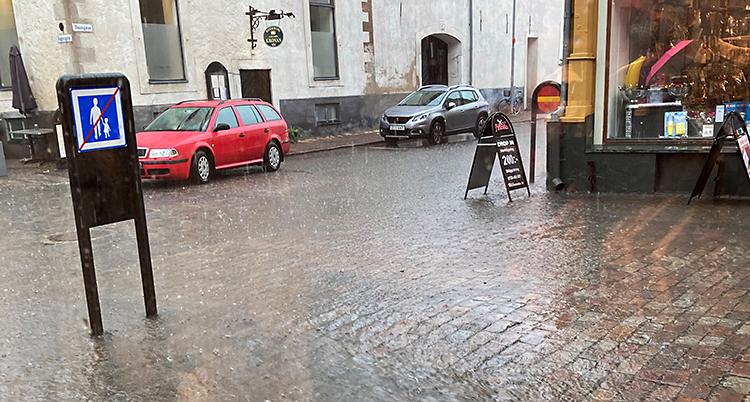 En bild från en gata som är fylld av vatten. Längs vägkanterna i staden står bilar.