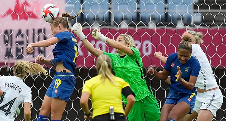 Från en match i fotboll. Många personer är framför målet. En person nickar bollen.