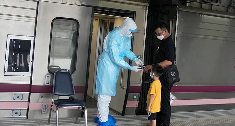 Bild på sjukvårdare som undersöker människor som ska åka tåg i Thailand.