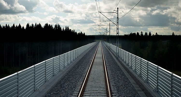 En bild på en järnväg som går genom en skog.