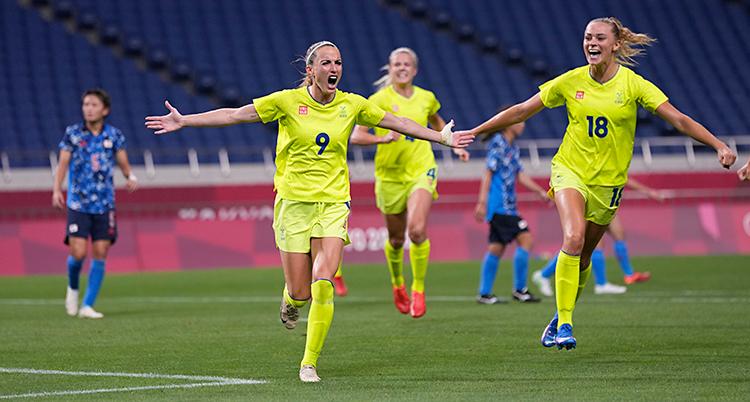 Från en match i fotboll. Kosovare Asllani springer och ropar av glädje. Flera spelare springer fram mot henne. Alla har gula kläder.