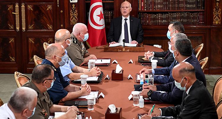 Tio män sitter vid ett bord. Längst bort sitter en man på kortsidan av bordet. Det är presidenten.