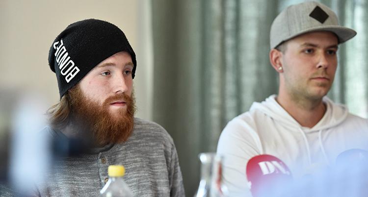 De sitter bredvid varandra. Mannen till vänster har svart mössa och rött skägg. Mannen till höger har vit tröja och grå keps. De sitter framför mikrofoner.