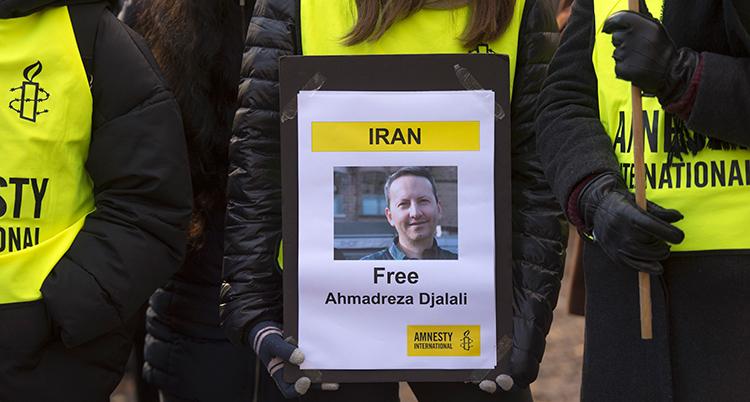 MÄnniskor i gula västar som det står Amnesty på, håller ett plakat framför sig med bild på Djalali och en krav på att han blir fri.