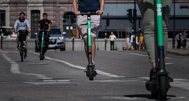 En bild från en gata i Stockholm där riksdagen syns i bakgrunden. I förgrunden syns underdelen av två gröna elsparkcyklar. En bit bort kommer två personer på cyklar.