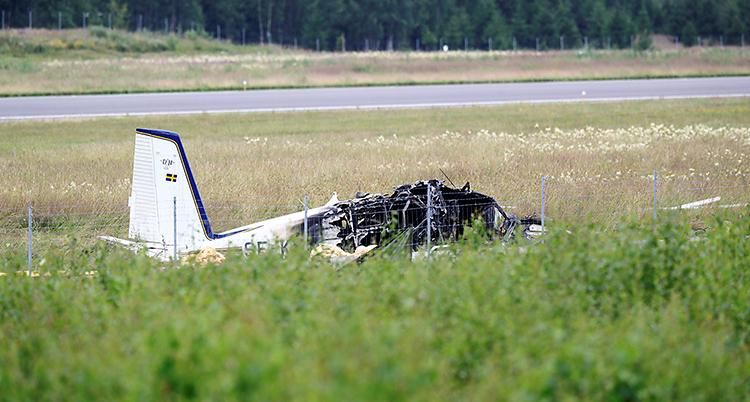 Flygplanet ligger på marken i gräset. Fotot är taget en bit ifrån. Fören på flygplanet är utbrunnet. Bakdelen ser intakt ut.