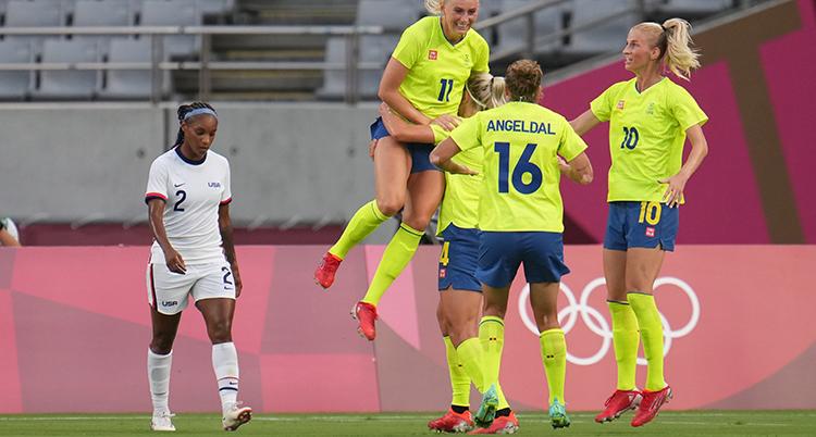 Hon har gul fotbollströja och hoppar upp i luften. Med kameran mot ryggen står en till spelare med gul tröja och en tredje i profil. De är glada. Till vänster går en spelare i vit tröja med besviken min.