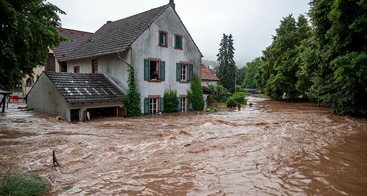 Ett hus står mitt i en kraftig översvämning. Vattnet går upp en bit på fasaden.