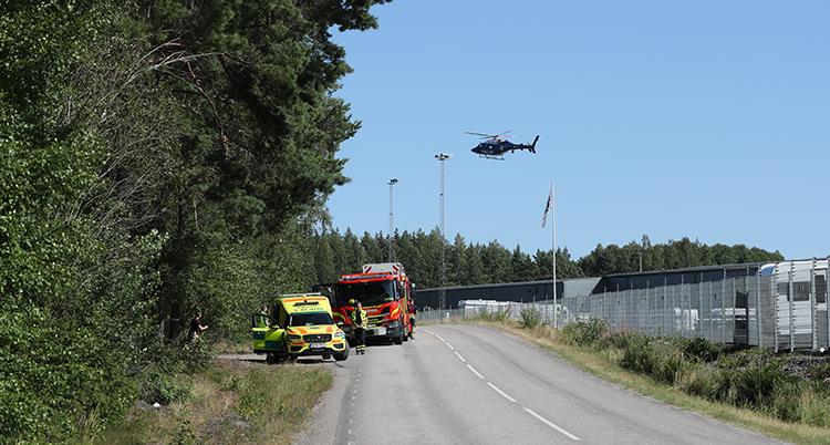 En gul ambulans och en röd bil från räddningstjänsten står vid sidan av vägen, en helikopter flyger i luften och på höger sida ses en del av det grå fängelset bakom ett nätstängsel.
