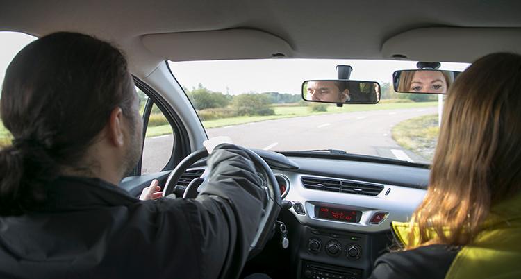 Han sitter bakom ratten i en bil, med ryggen mot kameran, och har händerna på ratten. Ögonen syns i backspegeln. Bredvid sitter en kvinna. Hennes ögon syns också i en backspegel.
