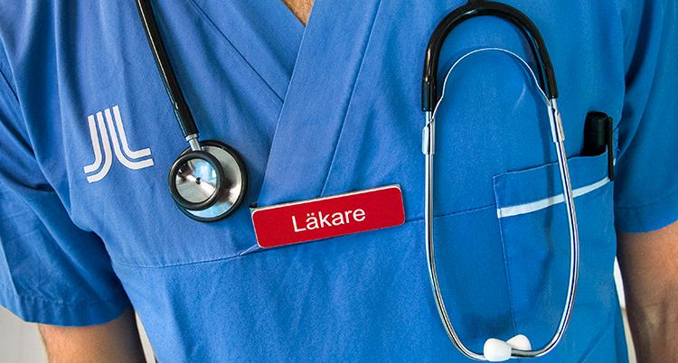 ´Läkare`står det på en röd namnskylt som sitter på en blå tunika. Runt halsen har personen ett stetoskop. Bara en del av överkroppen syns.