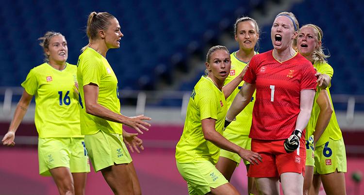 Fler fotbollsspelare i gula tröjor rör sig mot målvakten i röd tröja. Målvakten skriker.