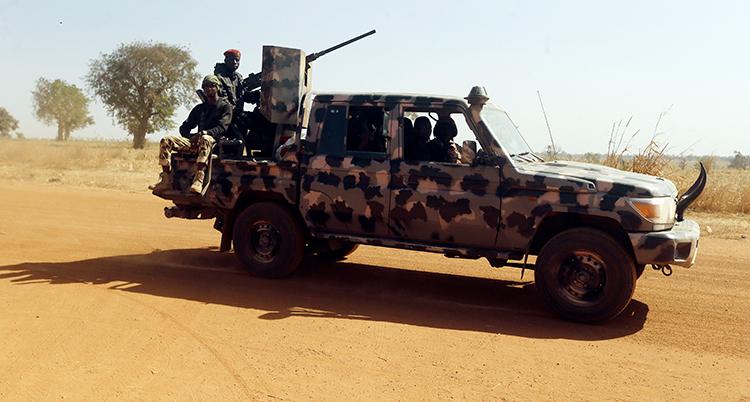 Fler män med vapen åker i en bil.